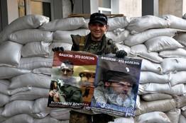 """26-го июля пророссийский повстанец в Лисичанске (Украина) держит плакаты, на которых по-русски написано: """"Фашизм – это болезнь"""" и """"Встречайте доктора"""". Photo: Agence France-Presse/Getty Images"""