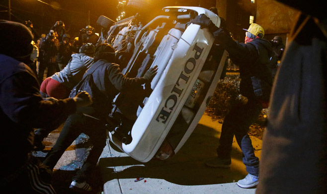 Protesters flip over a Ferguson police car in Ferguson, Missouri, Nov. 25.  Jim Young / Reuters