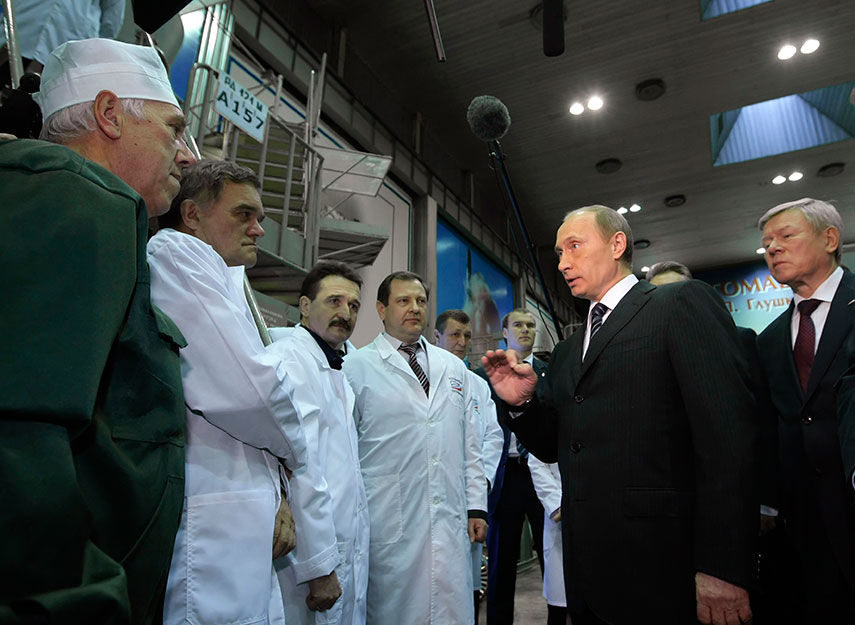 IN HIS ORBIT: President Vladimir Putin takes a close interest in Russia's space companies. Here, as prime minister in 2009, he talks to staff at Energomash, maker of the RD-180 engines that power U.S. Atlas V rockets. REUTERS/Ria Novosti/Pool/Alexei Nikolsky