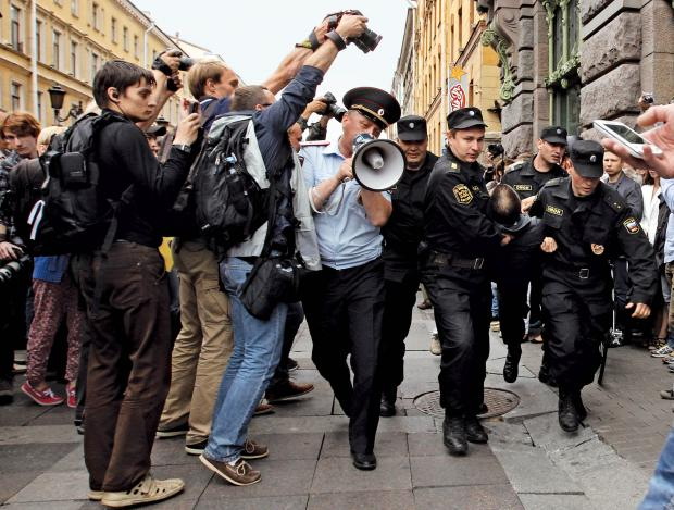 Photographers take pictures of riot police detaining a man during a protest in St. Petersburg, against a court verdict in Kirov sentencing Russian opposition leader Alexei Navalny to five years in jail, July 18, 2013