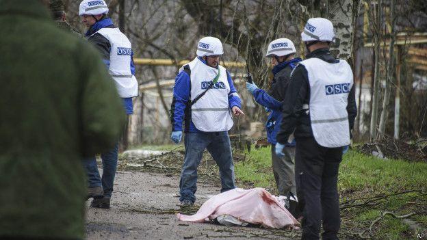 Сотрудники миссии ОБСЕ вокруг тела погибшего на востоке Украины