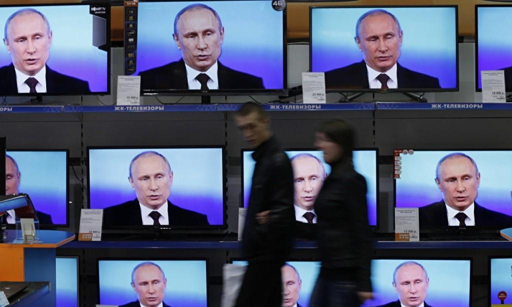 Покупатели в центральной части города Красноярска проходят мимо экранов, показывающих трансляцию Владимира Путина. Фото: Илья Наймушин / ИЛЬЯ Наймушин / Reuters / Corbis