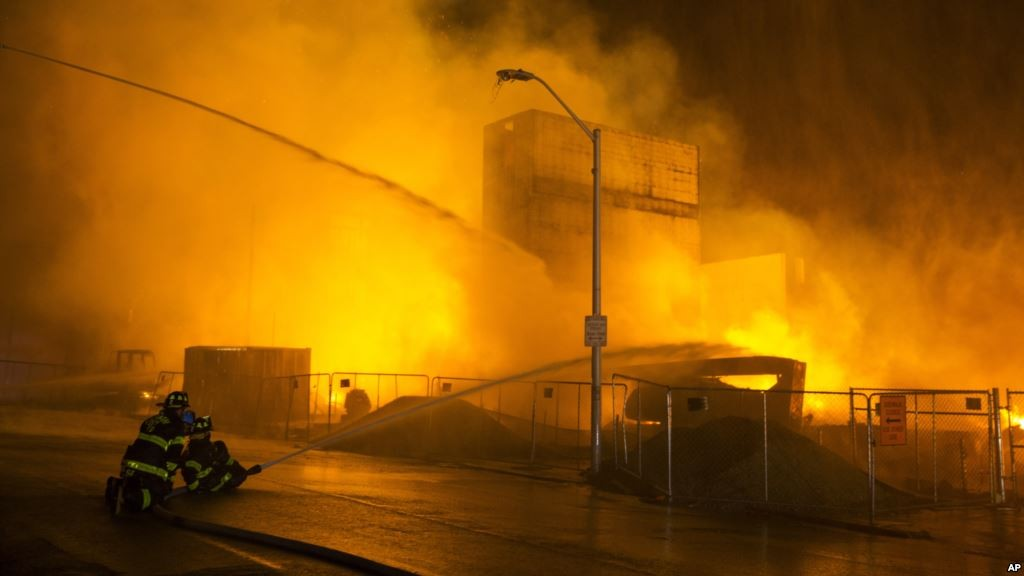 Firefighters battle a blaze, after rioters plunged part of Baltimore into chaos, torching a pharmacy, setting police cars ablaze and throwing bricks at officers, April 27, 2015.