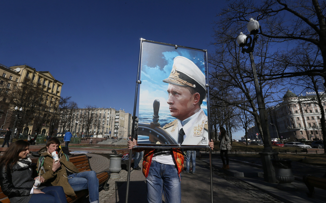 epaselect epa04664779 An activist of the Anti-Maidan movement installs an artwork representing Russian President Vladimir Putin during an outdoor exhibition entitled 'Crimea: Return to Home Port', in Moscow, Russia 16 March 2015. The exposition is devoted to the anniversary of the referendum in which the people voted for the Crimea entry into the Russian Federation.  EPA/YURI KOCHETKOV