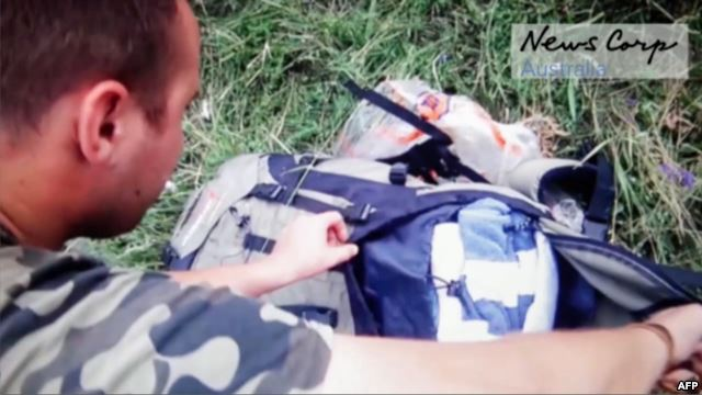 A screen grab taken from the News Corp video shows a Russian-backed rebel looking through the personal belongs of passengers at the site of downed Malaysia Airlines Flight MH17 shortly after it crashed.