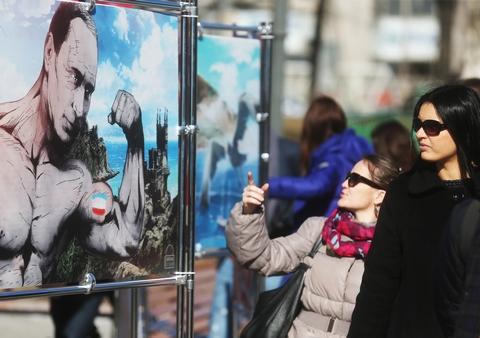 """MOSCOW, RUSSIA. MARCH 16, 2015. Posters on display at an exhibition titled """"Crimea. The return to its native harbor"""" in Moscow's Novopushkinsky Park. The exhibition marks the 1st anniversary of the 2014 Crimean status referendum. Sergei Fadeichev/TASS Ðîññèÿ. Ìîñêâà. 16 ìàðòà. Íà âûñòàâêå ãðàôè÷åñêèõ ðàáîò """"Êðûì. Âîçâðàùåíèå â ðîäíóþ ãàâàíü"""", ïîñâÿùåííîé ãîäîâùèíå ðåôåðåíäóìà â Êðûìó, â Íîâîïóøêèíñêîì ñêâåðå. Ñåðãåé Ôàäåè÷åâ/ÒÀÑÑ"""