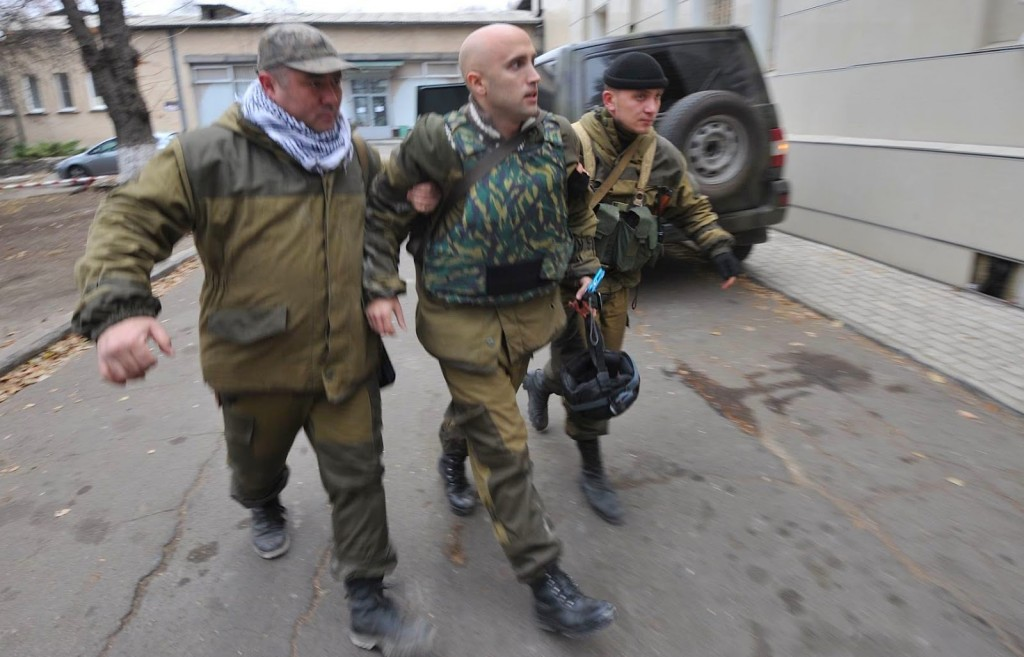 Graham Phillips (center) escorted by Russia's DNR soldiers after being wounded in Ukraine on Nov 24th 2014