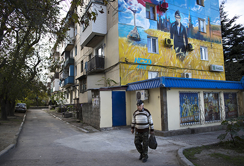 In this photo taken on Sunday, Oct.  26, 2014, a man in Russian Navy hat walks past a mural on an apartment building depicting Russian President Vladimir Putin in a navy uniform with the Kremlin and a Russian flag in the background in Sevastopol,  Crimea. Russia on Saturday dismissed new U.S. sanctions as useless and said it was poised to wait as long as it takes for the U.S. to recognize its historic right to the Crimean peninsula. Following several rounds of sanctions earlier this year, President Barack Obama on Friday approved new restrictions on Crimea which Russia annexed in March after a hastily called referendum.(AP Photo/Alexander Zemlianichenko)