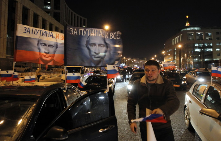 epa03112208 Activists of pro-Russian President Vladimir Putin's movement decorate their own cars with flags and portraits of Russian Prime Minister and presidential candidate Vladimir Putin during a propaganda car convoy action in Moscow, Russia, 18 February 2012. Russian presidential elections are scheduled on 04 March.  EPA/YURI KOCHETKOV