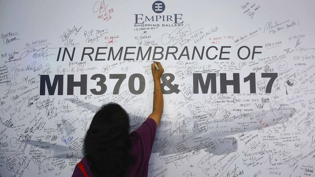 A woman writes a message on a dedication board for the victims of the downed Malaysia Airlines Flight MH17 airliner and the missing Flight MH370, in Subang Jaya outside Kuala Lumpur July 23, 2014. All sides in Ukraine's civil war must protect civilians and take what measures they can to search for the victims of downed Malaysia Airlines flight MH17 airliner and ensure their bodies are returned, the International Committee of the Red Cross said on Wednesday.REUTERS/Samsul Said (MALAYSIA - Tags: DISASTER TRANSPORT POLITICS SOCIETY)