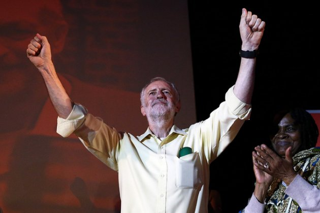 LONDON, ENGLAND - AUGUST 03: Jeremy Corbyn raises his arms in the air after speaking to supporters at a Labour party leadership rally on August 3, 2015 in London, England. Campaigning for Labour party leadership is continuing by all candidates with polls putting Jeremy Corbyn currently in the lead. Voting is due to begin on the 14th August and will close on the 10th September, with the results being announced on the 12th September. (Photo by Carl Court/Getty Images)