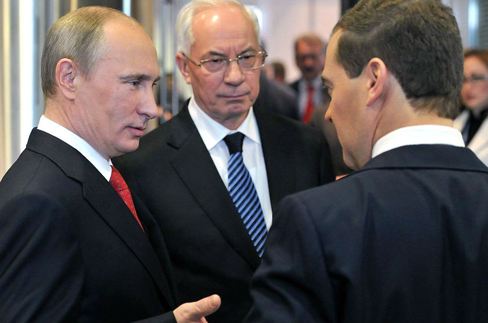"Russian President Vladimir Putin and Russian Prime Minister Dmitry Medvedev at a meeting with former Ukrainian Prime Minister Mykola Azarov on May 26, 2012 in Moscow, Russia. On August 3, Azarov—now living in exile in Moscow—formed the ""Ukraine Salvation Committee,"" whose goal is ""regime change"" back home. Azarov is wanted in Ukraine for several crimes including embezzlement and abuse of power. Credit: Kremlin.ru"