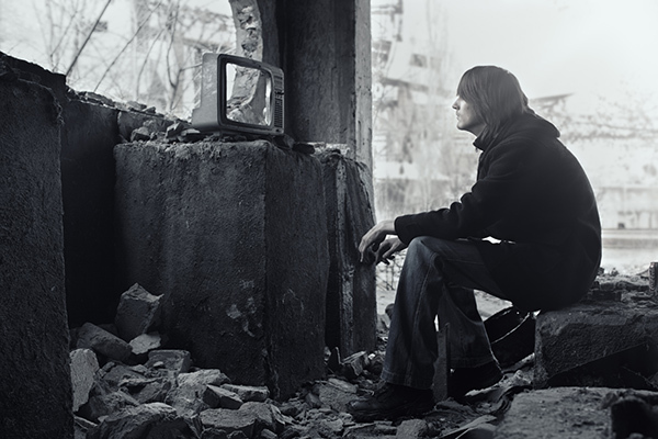 Homeless man watching broken TV-set in the ruined interior. Shallow depth of field due to the tilt lens for movie effect