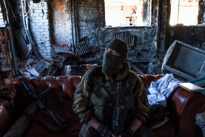 """A Russia-backed rebel in eastern Ukraine on Tuesday. Russia has used """"hybrid war"""" tactics to mask its operations there. Credit Mstyslav Chernov/Associated Press"""