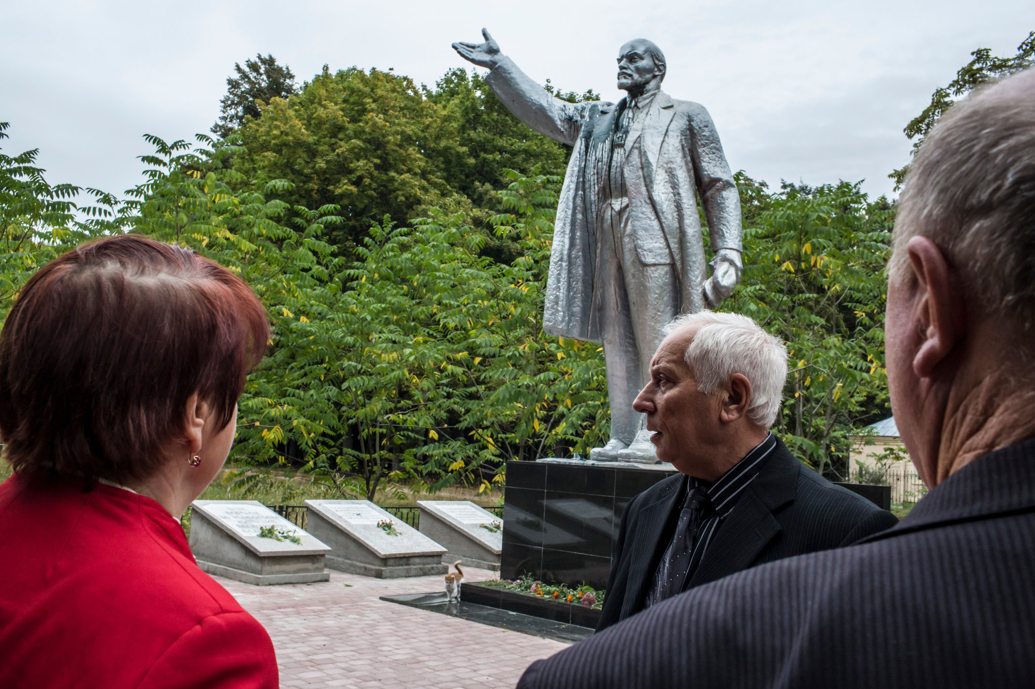 Ivan Papchenko, center, and the Lenin statue moved from town square to a remote spot in a park in Semyonovka, Ukraine. Credit Brendan Hoffman for The New York Times