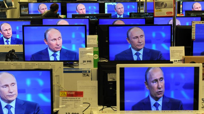 A customer walks past the TV screens in a shop in Moscow, on April 25, 2013, during the broadcast of President Vladimir Putin's televised question and answer session with the nation. AFP PHOTO / ANDREY SMIRNOV        (Photo credit should read ANDREY SMIRNOV/AFP/Getty Images)