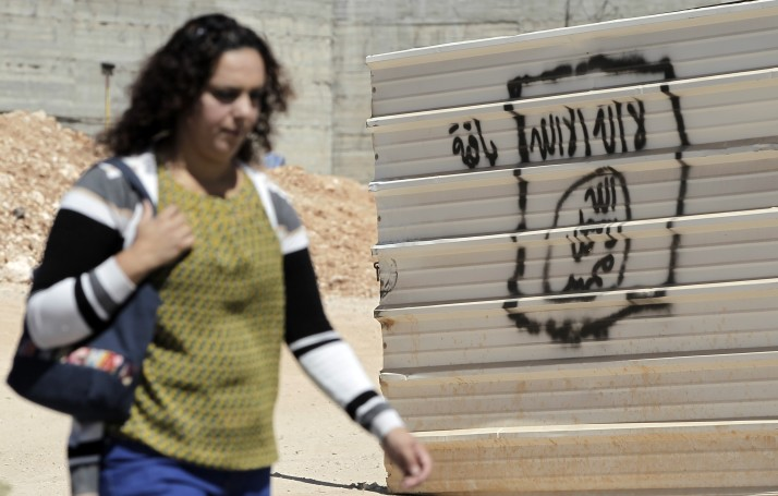 A woman walks past a graffiti portraying the Islamic State (IS) group's flag in the East Jerusalem neighbourhood of Beit Hanina on July 5, 2015. AFP PHOTO / AHMAD GHARABLI (Photo credit should read AHMAD GHARABLI/AFP/Getty Images)