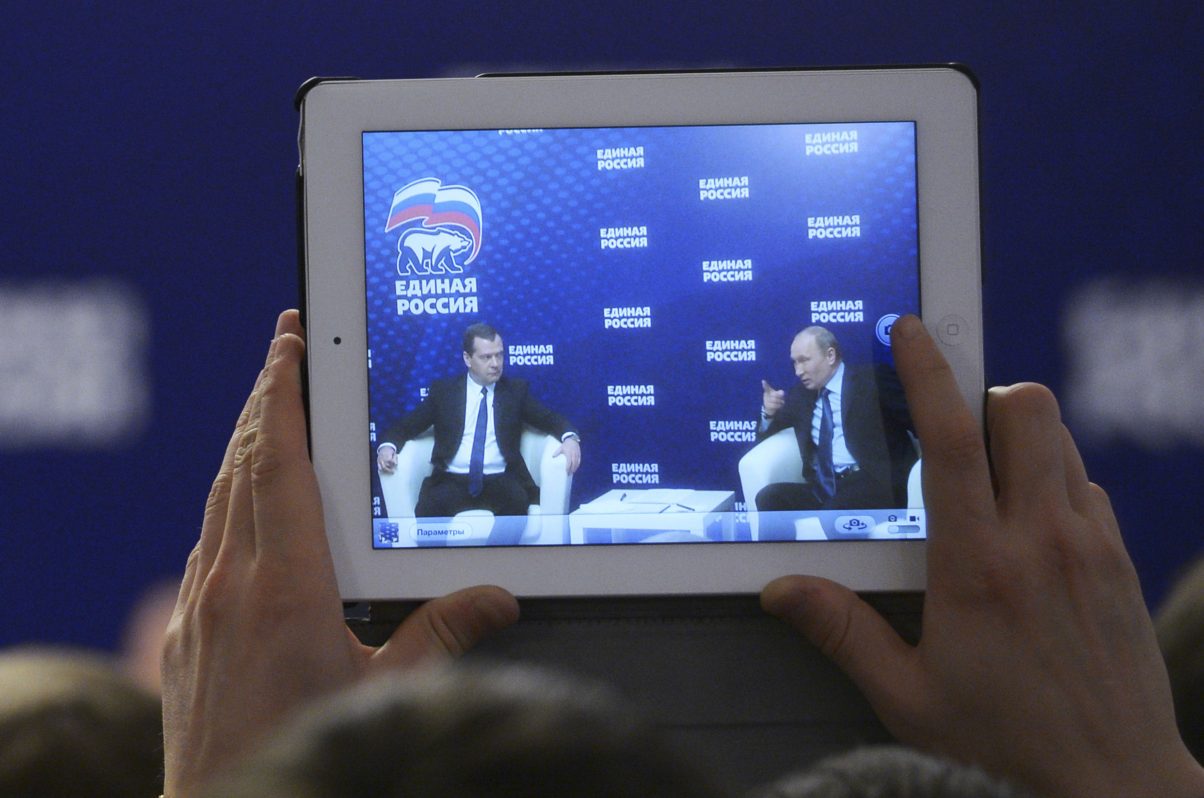 Russia's President Vladimir Putin (R) and Prime Minister Dmitry Medvedev are seen on a screen of a tablet computer during a meeting with members and activists of the United Russia political party in Moscow region, October 3, 2013. Credit: REUTERS/Alexander Astafyev/RIA Novosti/Pool