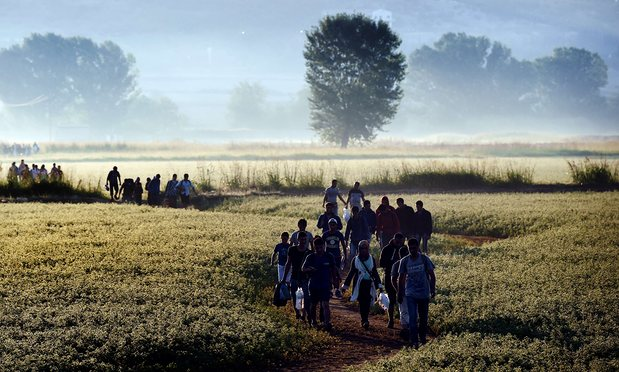 Syrian refugees cross the border between Greece and Macedonia in 2015. Photograph: Aris Messinis/AFP/Getty Images