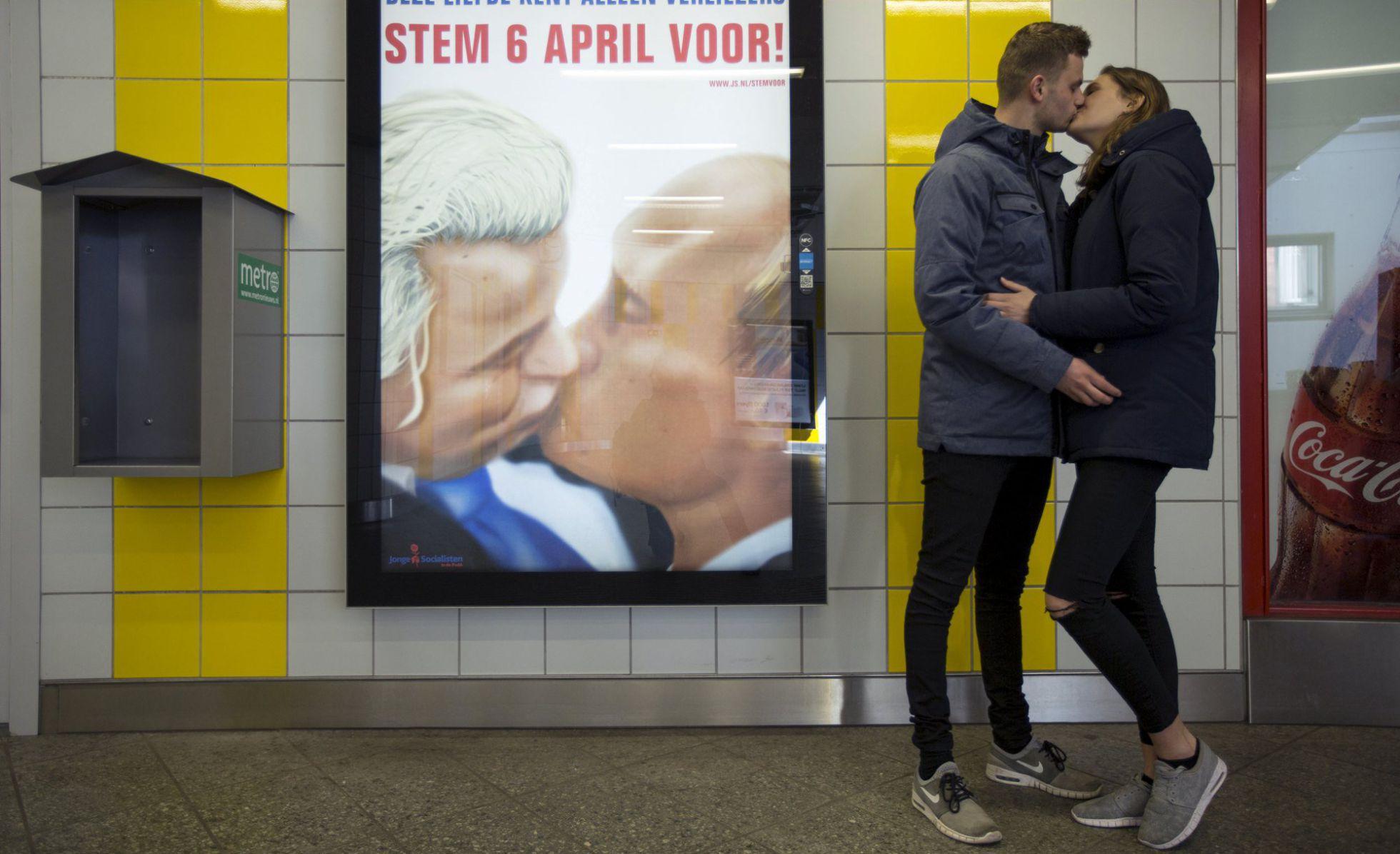 Una pareja se besa junto a un poster con una caricatura en la que el político holandés Geert Wilders besa al presidente ruso Valdímir Putin en el metro de Ámsterdam. Foto por Cris Toala Olivares, REUTERS