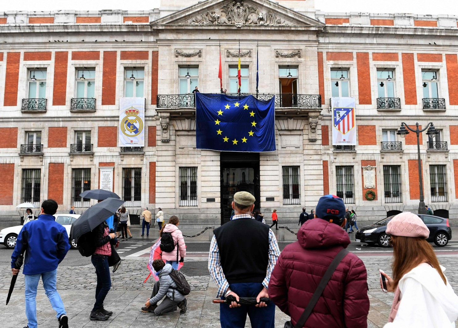 The European Union flag is displayed between two soccer club banners on the Royal Post Office, the seat of the office of the president of Madrid. (Gerard Julien/Agence France-Presse via Getty Images)