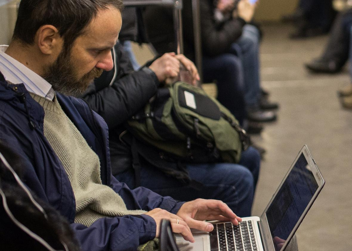 A commuter consult his laptop inside a train coach in the Moscow Metro, on Dec. 1, 2014. Photo by DMITRY SEREBRYAKOV/AFP/Getty Images