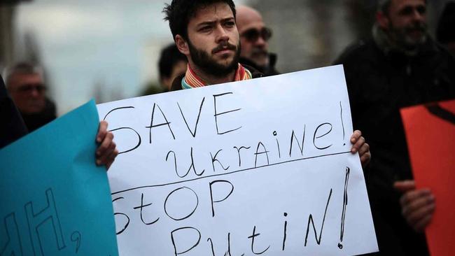 3 март 2014 г. София. Български демонстрант държи ръце платкат с надпис «Спасете Украйна, спрете Путин» по време на протестна акция пред руското посолство в столицата на България / Снимка THE ASSOCIATED PRESS