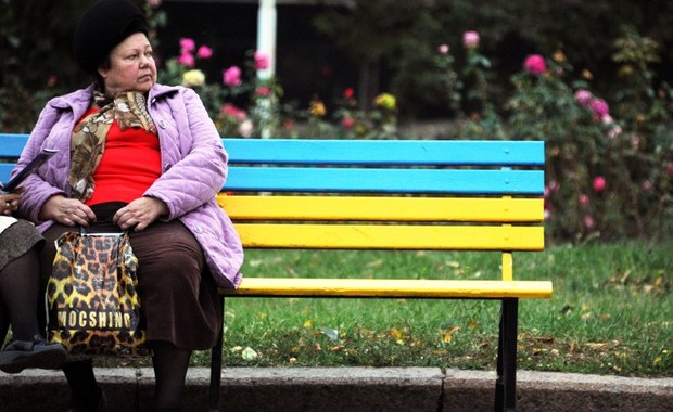 A woman sits on a bench painted in the colours of the Ukrainian national flag in Slavyansk, eastern Ukraine, on October 22, 2014. Ukraine's President Petro Poroshenko's party on October 22 led the final polls before Sunday's parliamentary vote held as the country faced an unresolved Russian gas dispute and raging hostilities in the east. AFP PHOTO / DOMINIQUE FAGET / AFP PHOTO / DOMINIQUE FAGET
