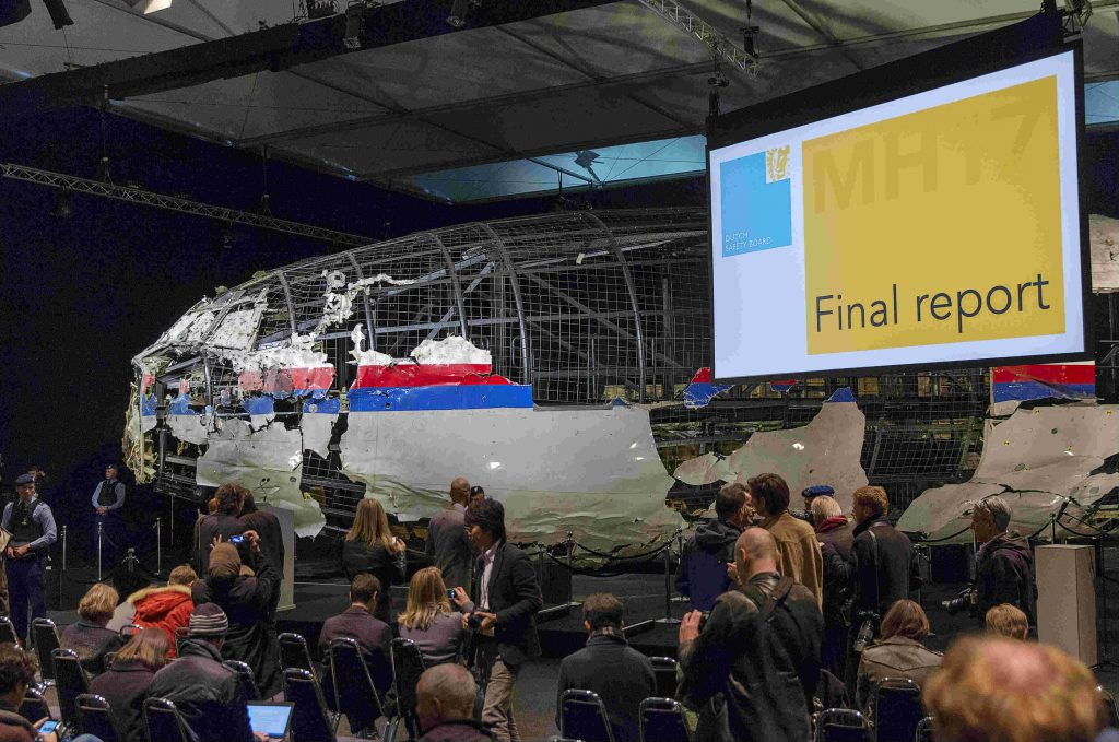 The reconstructed airplane serves as a backdrop during the presentation of the final report into the crash of July 2014 of Malaysia Airlines flight MH17 over Ukraine, in Gilze Rijen, the Netherlands, October 13, 2015. REUTERS/Michael Kooren