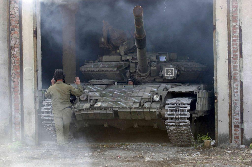 Член на военните сили на самообявената Луганска народна република помага на танк да се паркира след изтеглянето му от фронтовата линия до Луганск . REUTERS/Alexander Ermochenko (Atlantic Council)