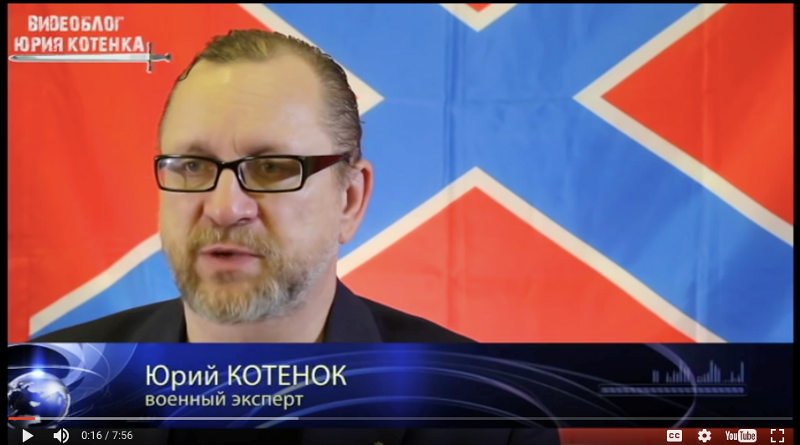 """Screen shot of Kotenok, as a """"military expert"""", in front of a flag often used by separatists"""