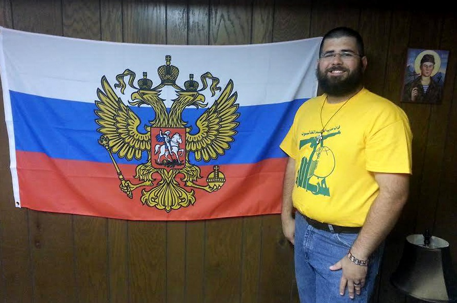 Matthew Heimbach stands next to a flag used to represent the president of Russia in a photo he published to his personal page on the Russian social media web site VKontakte in August 2015